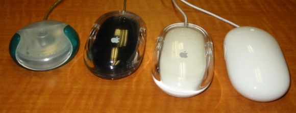 Four generations of awful mice from Cupertino: Apple Hockey Puck, Pro Mouse black & white, and the current Mighty Mouse.